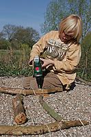 Kinder basteln Klangspiel aus Ästen, Junge bohrt mit Akkubohrer ein Loch in den Rahmen-Ast