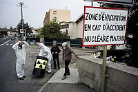 """Activists of the associative network Exit From Nuclear. They organize communication activities. Here, they hang a sign at the entrance of the city of Loyettes, 10 km from the plant of Bugey. Many residents work at the plant. Volunteers are not generally welcomed by residents who benefit, in one way or another, from the economic benefits associated with the presence of the nuclear site. They argue that day to put that common signs like this to alert citizens. In the event of a major accident, the city of Lyon would be directly affected, it is only 35 km.<br /> <br /> """"Fenêtre avec vue"""" est publié dans le journal suisse La couleur des jours, n°18, printemps 2016.<br /> http://www.lacouleurdesjours.ch/sommaires.php?ID=36<br /> <br /> <br /> Lire également, dans sa version """"réglementée"""":<br /> <br /> http://www.ladocumentationfrancaise.fr/pages-europe/pe000036-sortir-du-nucleaire-au-caeur-du-mix-energetique-suisse-par-alexandre-mouthon/article<br /> <br /> Lire dans sa version originale """"non réglementée"""":<br /> <br /> http://alencontre.org/suisse/sortir-du-nucleaire-le-coeur-du-mix-energetique-suisse-place-dans-sa-perspective-europeenne.html"""