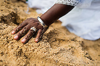 A hand of a Baiana woman in the sand seen during the festival of Yemanjá, the goddess of the sea, in Salvador, Bahia, Brazil, 2 February 2012. Yemanjá, originally from the ancient Yoruba mythology, is one of the most popular ?orixás?, the deities from the Afro-Brazilian religion of Candomblé. Every year on February 2nd, thousands of Yemanjá devotees participate in a colorful celebration in her honor. Faithful, usually dressed in the traditional white, gather on the beach at dawn to leave offerings for their goddess. Gifts for Yemanjá include flowers, perfumes or jewelry. Dancing in the circle and singing ancestral Yoruba prayers, sometimes the followers enter into a trance and become possessed by the spirits. Although Yemanjá is widely worshipped throughout Latin America, including south of Brazil, Uruguay, Cuba or Haiti, the most popular cult is maintained in Bahia, Brazil.