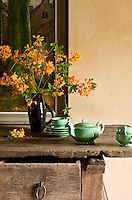 On a rustic sideboard in the kitchen a jade-green tea service and a simple jug of orange rhododendron flowers create a perfect still-life