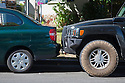 A H3 Hummer parked right up against the bumper of a Toyota Echo.The H3 gets 16 miles per gallon whereas the Echo gets 38 miles per gallon. Millbrae, California, USA