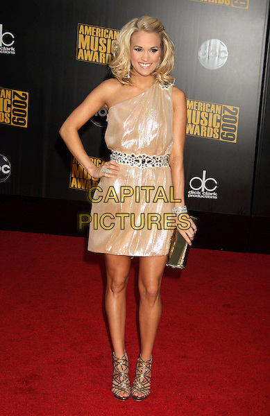 CARRIE UNDERWOOD .2009 American Music Awards - Arrivals held at the Nokia Theatre L.A. Live, Los Angeles, California, USA..November 22nd 2009.AMA AMA's AMAS full length dress one shoulder silver gold embellished jewel encrusted belt Waistband clutch bag sandals hand on hip strappy bracelet ring shiny .CAP/ADM/MJ.©Michael Jade/AdMedia/Capital Pictures.