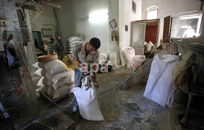 Palestinian laborers work at a Al-Adham old flour mill in the old town of West Bank city of Nablus October 10, 2017. Al-Adham mill Was founded in 1945 and grinds all kinds of grains, such as wheat, beans, chickpeas, on manual tools and still operate with the same system till our day says owner Naji Adham. Photo by Ayman Ameen