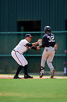 GCL Braves first baseman Ray Hernandez (46) puts a tag on Roberto Chirinos (32) as he runs up the first base line during the first game of a doubleheader against the GCL Yankees West on July 30, 2018 at Champion Stadium in Kissimmee, Florida.  GCL Yankees West defeated GCL Braves 7-5.  (Mike Janes/Four Seam Images)