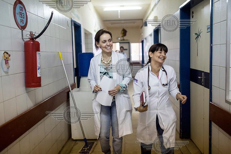 Speech therapist, Danielle Oliviera, right, and Dr. Regina Coeli, director of children's infectious diseases, walk down a corridor at Oswaldo Cruz University Hospital.