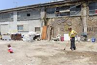 """Roma, 6 Giugno 2010.<br /> Metropoliz.<br /> Ex fabbrica abbandonata Fiorucci occupata ..L'edificio è occupato da un gruppo di Rom Romeni. .Festa con pranzo tradizionale e ciclofficina per finanziare i lavori di ristrutturazione..Una donna spazza il cortile.Rome, June 6, 2010.Fiorucci  abandoned factory busy..The building is occupied by a group of Romanian Roma..Celebration with traditional lunch and """"Ciclofficina""""(bicycle repair) to finance renovation.A woman sweeps the courtyard"""