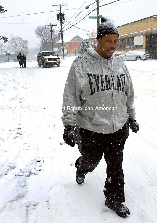 WATERBURY, CT. 21 January 2012-012112SV05-James Harris of Waterbury tries to make his way to his mothers house to help her during the snow storm in Waterbury Saturday. The area was dealing with a 3-6 inch snowstorm..Steven Valenti Republican-American