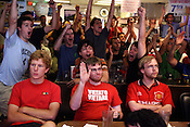 May 27, 2009. Chapel Hill, NC..Robert Laffoon, Tim Brown and Andrew Ashely sit in protest as Barcelona scores their second goal in the soccer game against Manchester while the rest of restaurant cheers..  Barcelona took the win at 2-0.