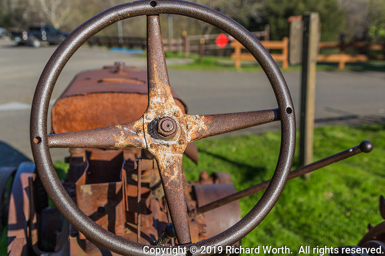 An antique John Deere tractor is among the farm implements scattered around the grounds at the Garin Regional Park in Hayward, California.