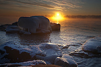 Ice covered boulders line the frozen shores of Lake Superior on Minnesota's north shore near Two Harbors. On cold days, the lake gives up its remaining warmth in the form of steam rising from its depths.
