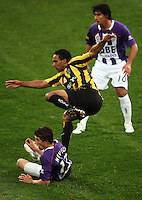 Phoenix striker Paul Ifill fires a shot at goal while the grounded Scott Neville and Wayne Srhoj look on during the A-League football match between Wellington Phoenix and Perth Glory at Westpac Stadium, Wellington, New Zealand on Sunday, 16 August 2009. Photo: Dave Lintott / lintottphoto.co.nz