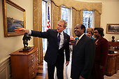 In this photo released by the White House, United States President George W. Bush and Laura Bush meet with Paul Rusesabagina and his wife, Tatiana, in the Oval Office Thursday, Feb. 17, 2005. The subject of the film, Hotel Rwanda, Mr. Rusesabagina sheltered refugees in a Rwandan hotel where he worked as a manager. <br /> Mandatory Credit: Eric Draper / White House via CNP