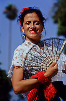 Portrait of smiling mexican woman in traditional costume holding a fan