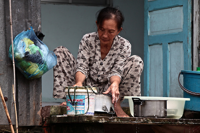 A woman washes dishes along the Hau River, in the Mekong Delta, south of Can Tho, Vietnam. Sept. 30, 2011.