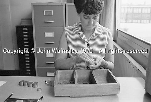 School secretary counting the dinner money, Whitworth Comprehensive School, Whitworth, Lancashire.  1970.