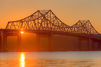 The sun sets behind the Tappan Zee Bridge and reflects off of the surface of the Hudson River as seen from Tarrytown, New York, USA
