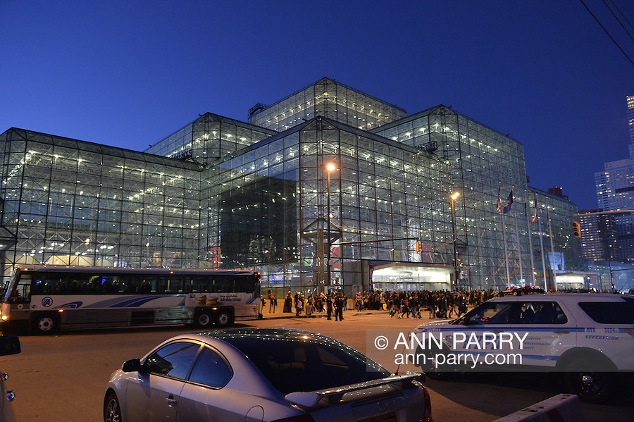 Manhattan, New York City, New York, USA. October 10, 2015. Outside the Javits Center, with its vast walls of glass, people are leaving on the third night, near 7 PM, of the 10th Annual New York Comic Con. A free Shuttle bus is outside the center, and visitors may take it to Penn Station, among other Manhattan destinations. An NYPD police car is parked across the street. NYCC 2015 is expected to be the biggest one ever, with over 160,000 attending during the 4 day ReedPOP event, from October 8 through Oct 11.