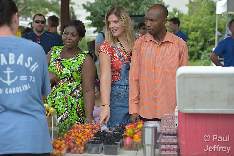 Monique Lohmeyer (center), a case manager for Church World Service, helps Casmil Ngundakumana (right) and Evanis Gatunzi (left), both refugees from Rwanda, navigate through the produce available in the Durham Farmers' Market in Durham, North Carolina. The market's Double Bucks program allows consumers with EBT cards to double their purchasing power.<br /> <br /> Church World Service resettles refugees in North Carolina and throughout the United States.<br /> <br /> Photo by Paul Jeffrey for Church World Service.