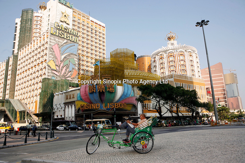 A cycle driver rests on the street in front of the Casino Lisboa, Macau. Next to it is the Wynn Casino. As restrictions on betting licsences have become open to tender international Casino operators such as Wynn, Sands and MGM are making huge investments into Macau which is becoming the Vegas of the East and is driven by the massive Chinese gambling market on the former Portuguese colony's doorstep...