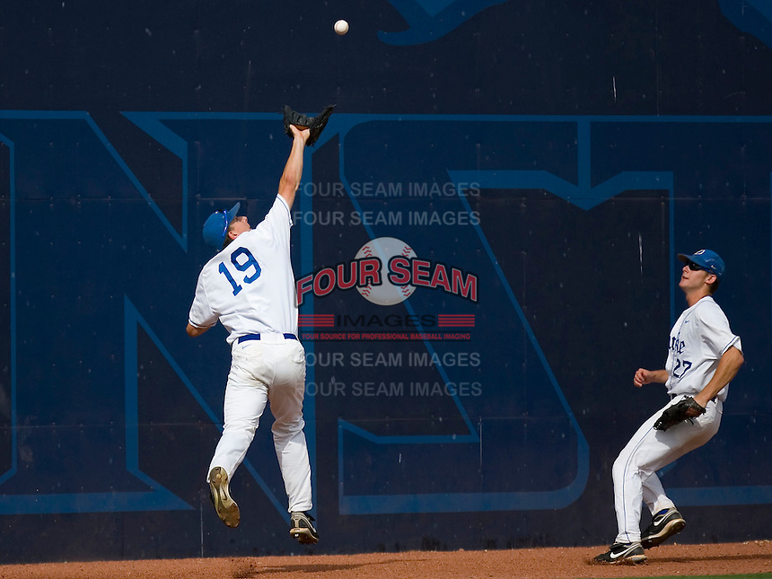 "Left fielder Jeremy Gould #19 of the Duke Blue Devils makes a catch in front of the ""Blue Monster"" at Durham Bulls Athletic Park May 22, 2009 in Durham, North Carolina.  (Photo by Brian Westerholt / Four Seam Images)"