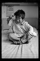 A Tibetan girl sits in bed before a cleft palate operation organized by Smile Angel Foundation at a hospital in Xining, Qinghai province, China, August 2013. (Names withheld for privacy)