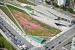 Aerial view of Seattle's Olympic Sculpture Park.  The Vivarium is a greenhouse-like structure housing a living nurse log salvaged from the foothills of the Cascade Mtns.  Elliott Avenue, a major thoroughfare visible lower left, runs underneath the park as native summer wildflowers bloom in the meadow areas overhead.