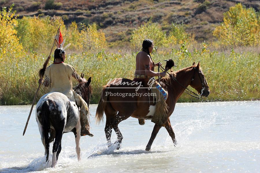 Two Native American Indian men on horseback walking through a river