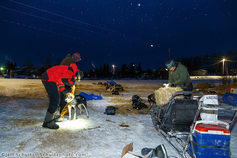 Volunteer veterinarians Scott Rosenbloom and Bruce Pedersen are given a dropped dog from Geir Idar Hjelvik in the early morning at the Kaltag checkpoint in on Sunday March 13th during the 2016 Iditarod.  Alaska    <br /> <br /> Photo by Jeff Schultz (C) 2016  ALL RIGHTS RESERVED