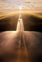 Two-lane road at sunrise or sunset with car and van in distance. United States.
