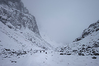 Two hikers in winter storm hike into remote valley on Moskenesøy, Lofoten Islands, Norway