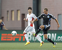 San Jose Earthquakes forward Adam Jahn (14) dribbles as New England Revolution defender Stephen McCarthy (15) closes. In a Major League Soccer (MLS) match, the New England Revolution (white) defeated San Jose Earthquakes (black), 2-0, at Gillette Stadium on July 6, 2013.