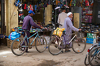 Rissani, Morocco.  Market Scene, Men with Bicycles Passing a Shoe Shop.