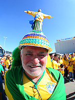 A Brazil fan with a Christ the Redeemer statue on his hat  soaks up the atmosphere outside the Itaquerao stadium ahead of kick off in the opening match of the 2014 World Cup vs Croatia