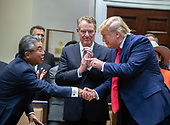 United States President Donald J. Trump, right, shakes hands with Ambassador Shinsuke Sugiyama, Ambassador of Japan to the US, left. after he signed the US-Japan Trade Agreement and US-Japan Digital Trade Agreement in the Roosevelt Room of the White House in Washington, DC on Monday, October 7, 2019.  Looking on at center is US Trade Representative Robert Lighthizer.<br /> Credit: Ron Sachs / Pool via CNP