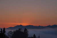 The sun sets behind the Olympics it's last light illuminates a Puget Sound fog bank.