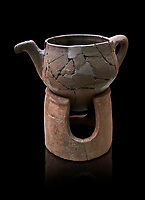 Hittite terra cotta teapot with strainer spout on a charcoa; burner base  . Hittite Period, 1600 - 1200 BC.  Hattusa Boğazkale. Çorum Archaeological Museum, Corum, Turkey. Against a black bacground.