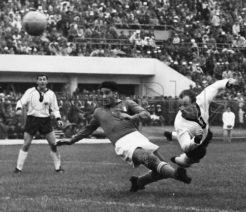 Diving German midfielder Uwe Seeler (R) heads toward the Italian goal while defender Radice (C) comes in too late and German teammate Hans Sturm (L) watches from a distance during the 1962 Soccer World Cup game.  Germany versus Italy at the National Stadium in Santiago de Chile, Chile, 31 May 1962. Germany and Italy played to a scoreless draw in front of 65,500 spectators.