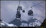 Austria, Kaprun.  Lines.<br /> All lines lead to the Kitzsteinhorn Gondola in the center of the image. The bottom peaks complement the gondolas and make a strong bottom frame. The stormy clouds add excitement and isolate the ski lift.