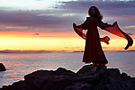 Artistic portrait of a young woman in long red dress flying in the wind dancing on the rocks of an ocean shore in sunset nature scenery