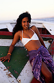 Itaparica Island, Bahia State, Brazil; girl in bikini and sarong reclining on a boat.