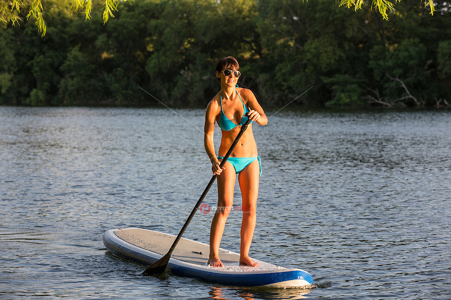 An athletic women smiling on a perfect sunny summer day while stand up paddle boarding SUP on Lady Bird Lake in Austin, Texas.