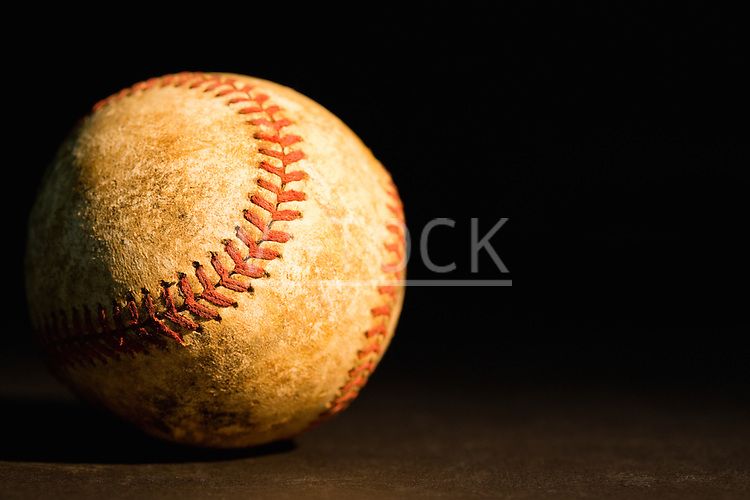 Old baseball against black background