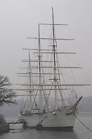 The Af Chapman three masted former school tall ship, now anchored off Skeppsholmen and functioning as a youth hostel. In foggy winter weather. Stockholm. Sweden, Europe.