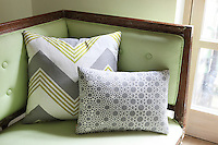 Detail of the white, green and grey, geometrically patterned scatter cushions on a newly upholstered antique sofa