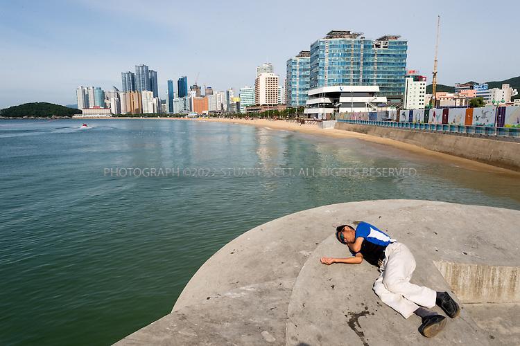 9/5/2013--Busan, South Korea<br /> <br /> A man sleeps off a hangover next to Haeundae Beach in Busan (Pusan).<br /> <br /> Photograph by Stuart Isett<br /> &copy;2013 Stuart Isett. All rights reserved.