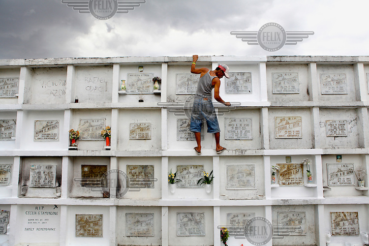 A man cleans and repaints tombs in Manila North Cemetery.