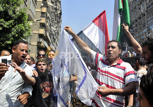 Egyptian demonstrators burn an Israeli flag during a protest outside the Israeli embassy in Cairo on August 20, 2011. Egypt decided to recall its ambassador from Israel to protest the deaths of policemen killed on the border, in the first diplomatic spat between the two nations since the fall of the Mubarak regime. Photo by Ahmed Asad