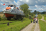 Boat on cable car being pulled uphill. Ostroda - Elblag Canal: Overland transportation of boats on rail cars at the Elblag Canal (Polish: Kanal Elblaskie, German: Oberlaendischer Kanal), Masuria, Poland, Europe. A system of rail-mounted cable trolleys on skipways and traditional locks are connecting the various sections of the Elblag Canal. A 100 metre difference in water levels is overcome during a length of 80 km between Ostroda and Elblag. The rail lift devices are mechanically driven by water power.--- HISTORY: The canal was designed in 1825-1844 by Georg Steenke, carrying out the commission given by the king of Prussia. Construction began in 1844. As the route was not important enough to justify building expensive, traditional locks between lakes, an ingenious system of tracks was employed instead, though the canal includes a few locks as well. Built originally under the name Oberländischer Kanal (Overland Canal) and situated in the Kingdom of Prussia, it was opened in 1860. Since 1945 the canal has been located in Poland. After wartime damage was repaired, it was restored to operation in 1948. Today it is used mainly for recreational purposes. It is considered one of the most significant monuments related to the history of technology on the territory of modern Poland..