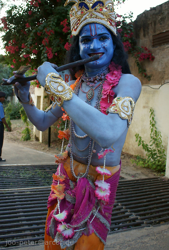 actor performing as krishna in street procession plays flute  in Pushkar, Rajastan, India
