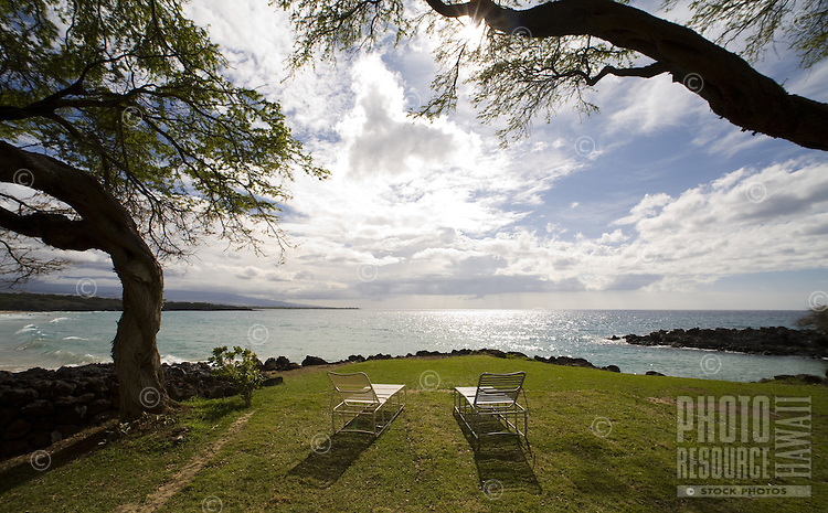 A couple of lawn chairs on the grounds of an oceanfront resort on the Big Island of Hawaii